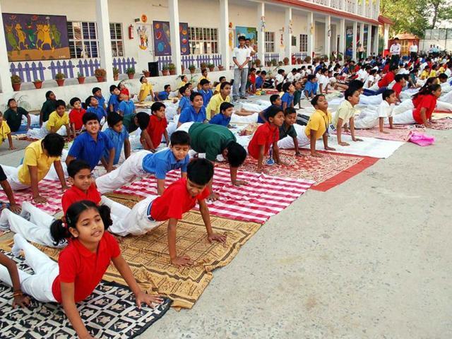 "Schoolchildren participate in a yoga class in Mirzapur, Uttar Pradesh. All India Muslim Personal Law Board member Maulana Sajjad Nomani has accused the BJP-led NDA government of ""thrusting"" the ""Hindutva"" on citizens."