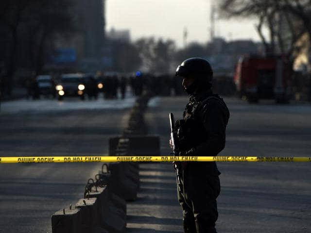 An Afghan security personnel stands guard near the site of an attack in Kabul. A 10-year-old Afghan boy who was hailed a hero after fighting the Taliban has been shot dead by insurgents.