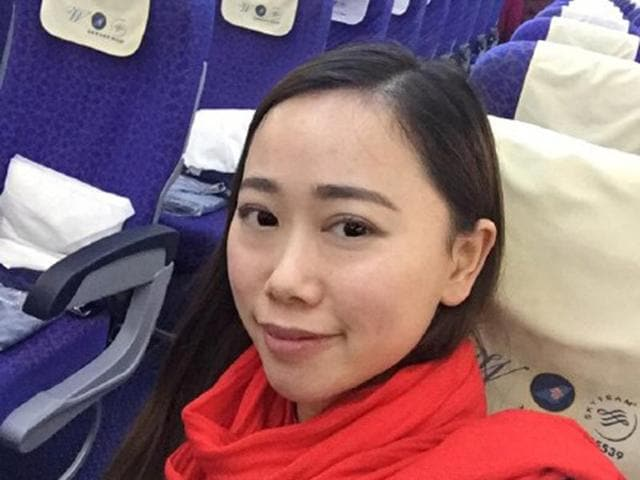 This photo taken on February 1, 2016 shows a Chinese woman surnamed Zhang taking photos with her mobile phone on an empty flight from Wuhan to Guangzhou, after the China Southern flight was delayed for 10 hours.
