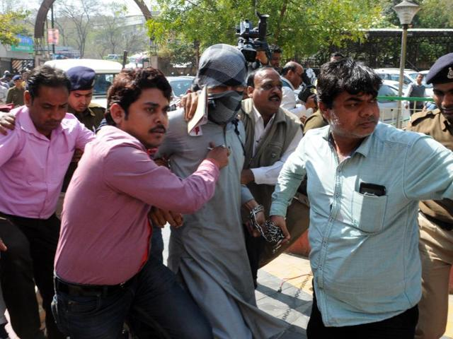 NIA officials produce suspected Islamic State operative Azhar Iqbal (centre) at the district court in Bhopal on Tuesday.