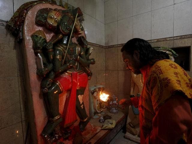 A priest holds an oil lamp to offer prayers in front of a deity at the Shri Panchmukhi Temple in Karachi.