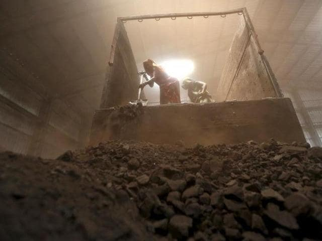 Workers unload coal from a supply truck at a yard on the outskirts of Ahmedabad.