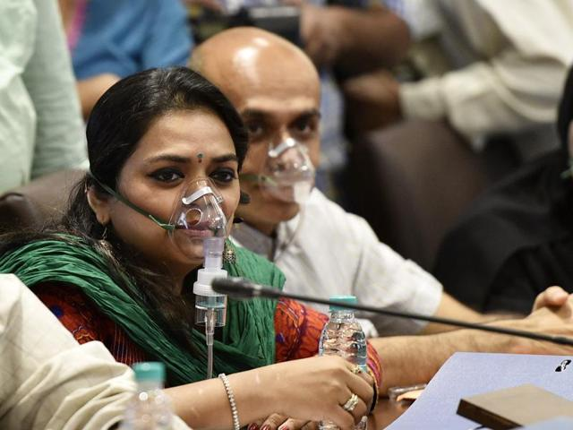 Congress corporators wear oxygen masks during the BMC's budget session to protest against the pollution caused by the Deonar dumping ground fire, on Wednesday.