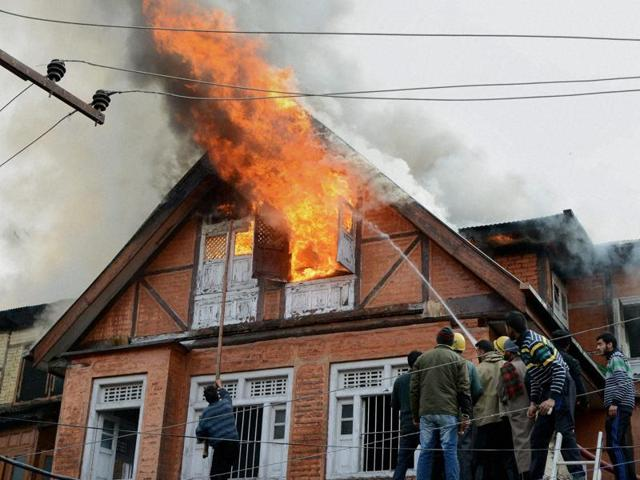 Fire fighters and locals trying to douse fire at Zaina Kadal in Srinagar on Thursday.