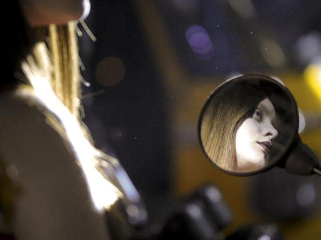 A model at the auto event is reflected in the rear view mirror of a motorbike. (Sunil Ghosh/ HT Photo)