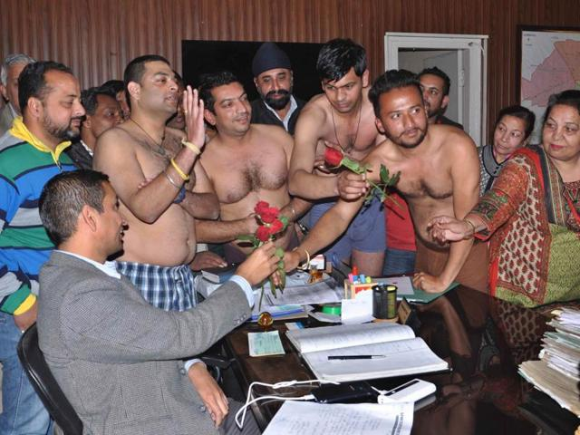 Taking off their clothes as mark of the protest, residents of Bawa Colony presenting flowers to a municipal corporation official in Ludhiana on Thursday.