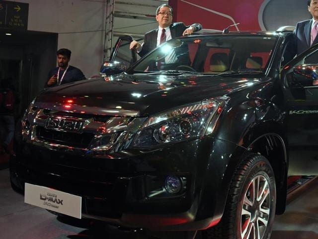 Susumu Hosoi, chairman and representative director of Isuzu Motors (R) and Naohiro Yamaguchi (L), managing director of Isuzu Motors India, poses with the newly launched Isuzu SUV at the Indian Auto Expo 2016 in Greater Noida on Thursday.