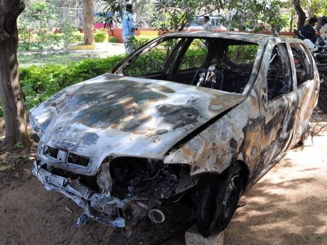 Indian pedestrians walk past the spot where a vehicle was set ablaze by a mob in Bangalore.