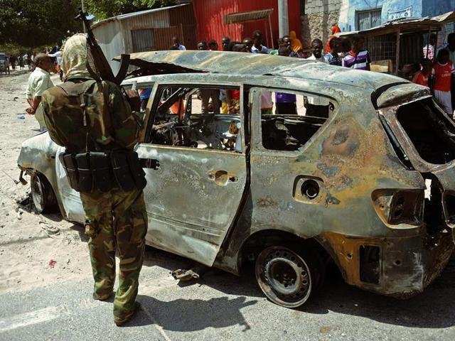 A soldier stands near a burnt car at the scene of a car bomb on February, 5, 2016 in Mogadishu.