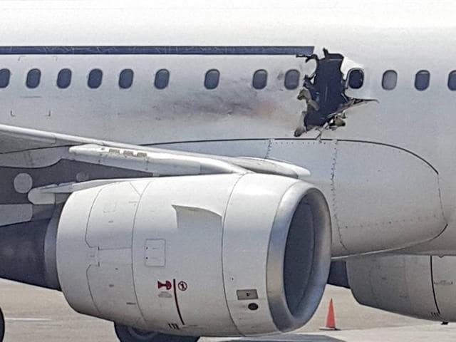 A hole is seen in a plane operated by Daallo Airlines as it sits on the runway of the airport in Mogadishu, Somalia.