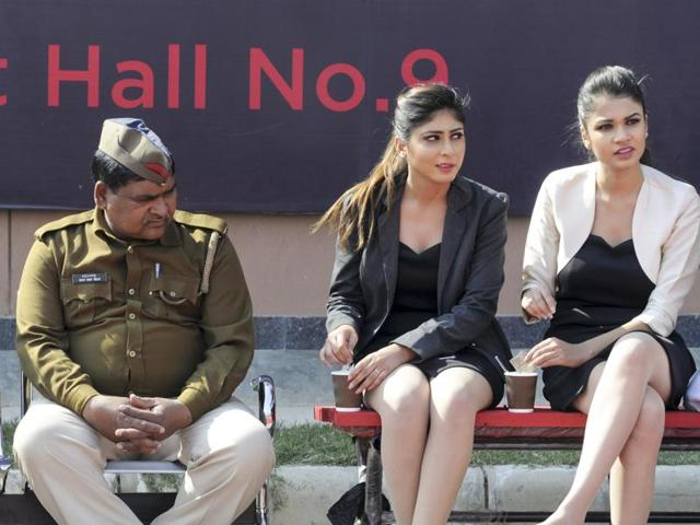 """Models participating in the Delhi Auto Expo take a lunch break. They can earn as much as Rs 10,000 a day for """"adding glamour"""" to the event."""