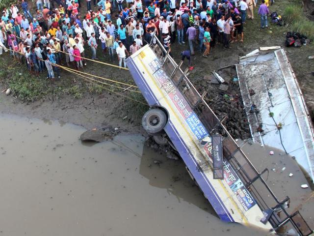 People carry out rescue work after a state transport bus fell off a bridge into the Purna river.