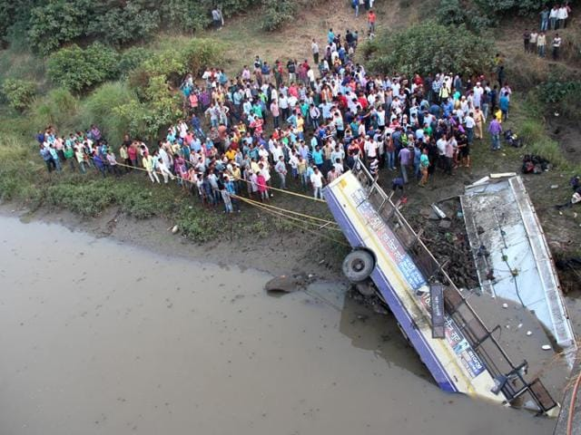 Locals gather in an attempt to rescue injured and recover bodies of passengers from the wreckage of the bus, in Navsari district of Indian state of Gujarat, Friday, Feb. 5, 2016.