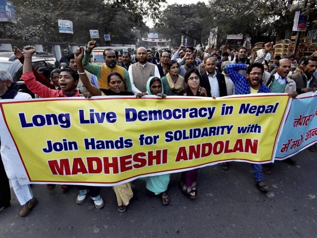 Nepalese lawmakers stage a protest as other lawmakers vote a constitution amendment bill in Kathmandu on January 23. Nepal's parliament voted to amend the country's new constitution in a bid to resolve a months-long dispute with Madhesis demanding more political representation.