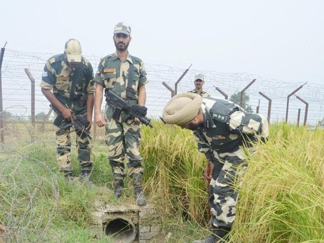 BSF personnel inspect the body of one of the four smugglers shot dead along the Indo-Pak border. Ten kilograms of contraband, arms and Pakistani currency was seized from the smugglers' possession.