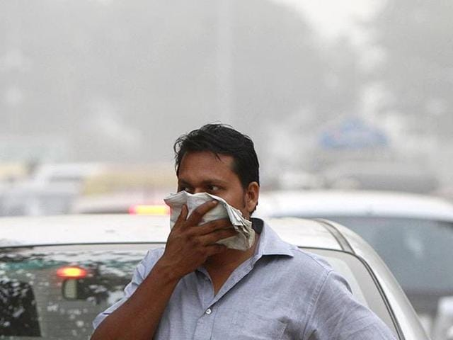 A man covers his face on a smoggy day in New Delhi. Jaguar Land Rover has criticised the ban on diesel vehicles' sale due to alarming levels of pollution