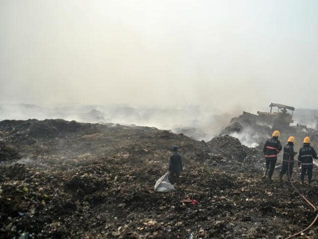 Fire safety officials extinguishing a fire at Deonar Dumping Ground in Shivaji Nagar in Mumbai. India's cities are struggling to cope with managing their waste output, largely due to that vast difference between official procedures and de facto management systems.(HT Photo)