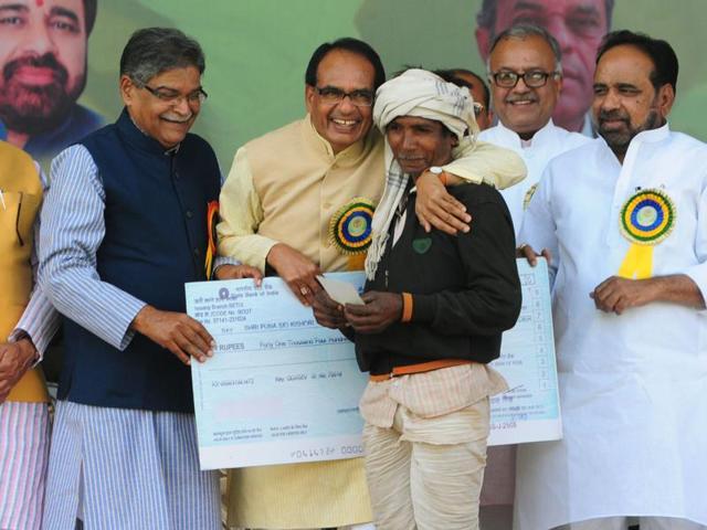 Chief minister Shivraj Singh Chouhan handing over bonus cheque to a tendu leaf plucker in Bhopal on Sunday.