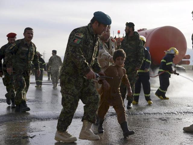An Afghan army officer escorts a slightly injured boy from the site of a suicide attack on the outskirts of Mazar-i-Sharif, Afghanistan.