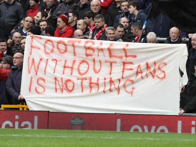 Liverpool fans hold up signs that says 'football without fans is nothing' in protest against the ticket prices .