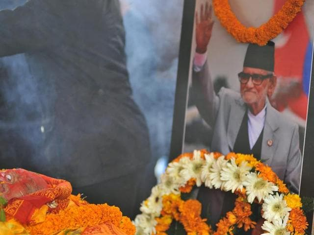 The body of Nepali Congress Party president Sushil Koirala (L) is covered in flowers as tributes are paid to him in Kathmandu.