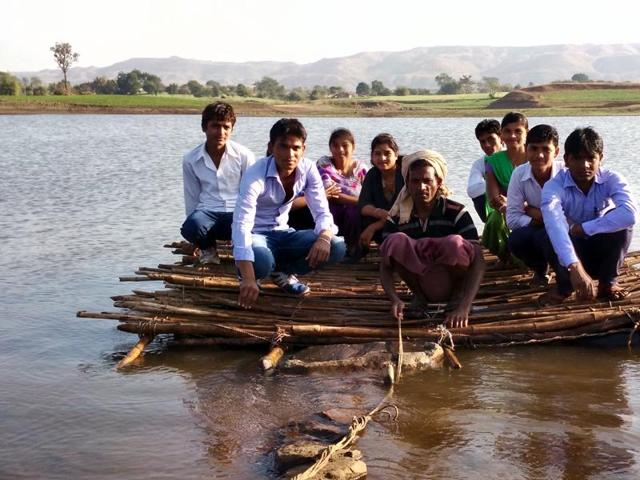People use a makeshift boat to cross backwater at Dhanora village in Barwani.