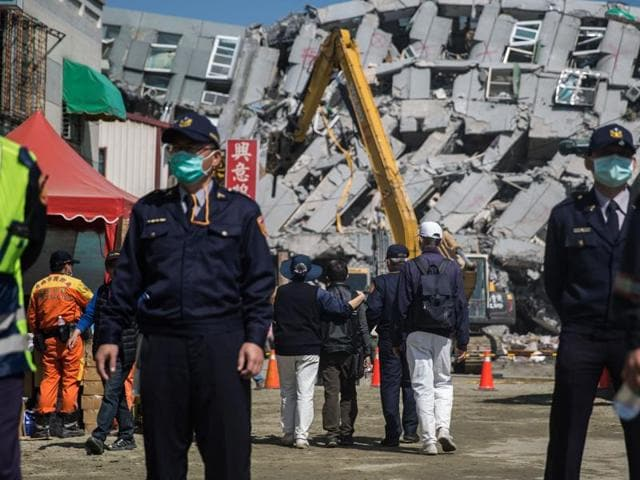 A general view shows excavator vehicles and rescue workers in front of a building (background) which collapsed in the 6.4 magnitude earthquake in the southern Taiwanese city of Tainan on February 9, 2016.