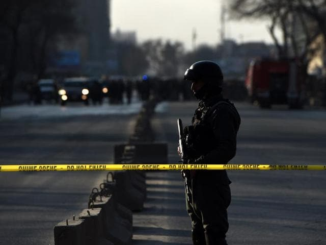 An Afghan security personnel stands guard near the site of an attack in Kabul.