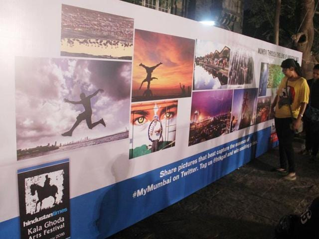 Visitors sit in front of the HT photo wall at the festival.
