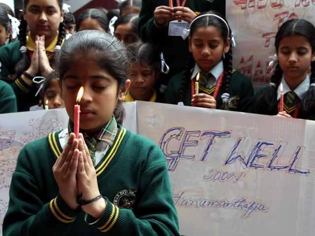 School children in Jammu pray and hold placards as they pray for Siachen avalanche survivor Lance Naik Hanumanthappa.