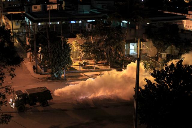 A military truck carries out fumigation in a neighborhood to stop the breeding of the dengue mosquito in Havana February 9, 2016.