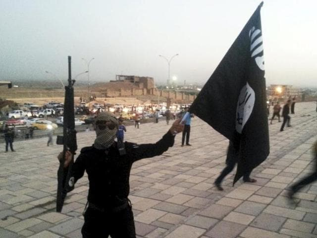 A fighter of the Islamic State shows group's flag and a weapon on a street in the city of Mosul.