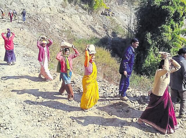 Villagers from the mountainous Maniyarsuen area carry materials for building the road on Wednesday.