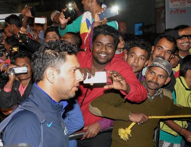 Harbhajan Singh, Rohit Sharma and Suresh Raina see the bright side as fans jouster to take pictures upon their arrival at the airport in Ranchi, Jharkhand, on Wednesday.