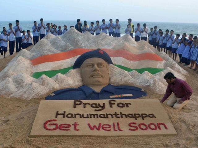 Students stand and pray near a sand sculpture created by Sudarsan Pattnaik of Hanamanthappa Koppad.