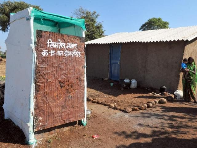 A woman in Indore's Nayagaon village stands in front of a toilet built on Simrol model of low-budget toilets.