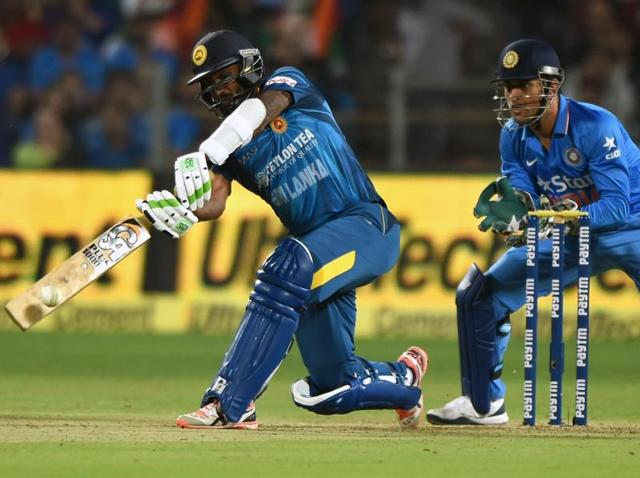 India's Mahendra Singh Dhoni (R) reacts as Sri Lanka's Chamara Kapugedera plays a shot during the first T20 international match between India and Sri Lanka at the MCA International Cricket Stadium in Pune on February 9, 2016.