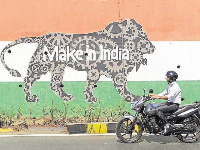 A motorist rides past a wall bearing the image of the mascot for 'Make in India Week' in Mumbai.