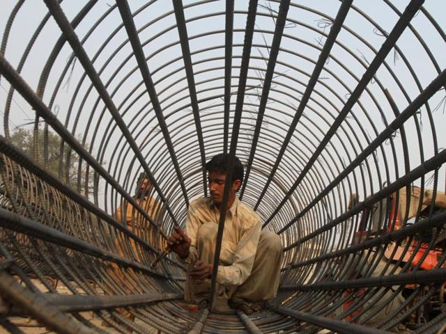 A labourers fixes a steel structure for the construction of a bridge in Lahore.