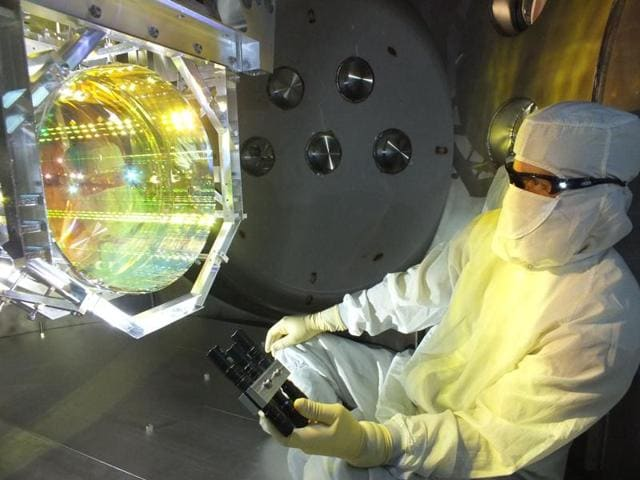 In this handout image taken December 14, 2015, provided by Caltech/MIT/LIGO Lab shows a Laser Interferometer Gravitational Wave Observatory (LIGO) optics technician inspecting one of LIGO's core optics . The world's third LIGO will be set up in India.