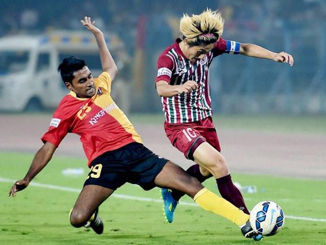 Soumik Dey of East Bengal and Katsumi Yusa of Mohun Bagan vie for the ball during their I-League match.
