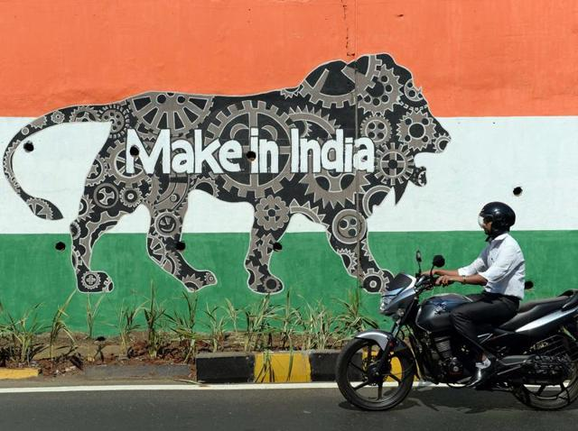 A motorist rides past a wall bearing the image of the mascot for the 'Make in India Week' in Mumbai. Over 10,000 security personnel have been deployed for PM Modi's visit to the financial capital.