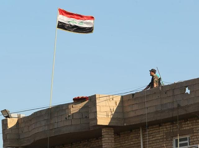 An Iraqi policeman in charge of the security in Ramadi stands on a roof on Saturday, after security forces retook the eastern outskirts of the city from Islamic State (IS) group jihadists.