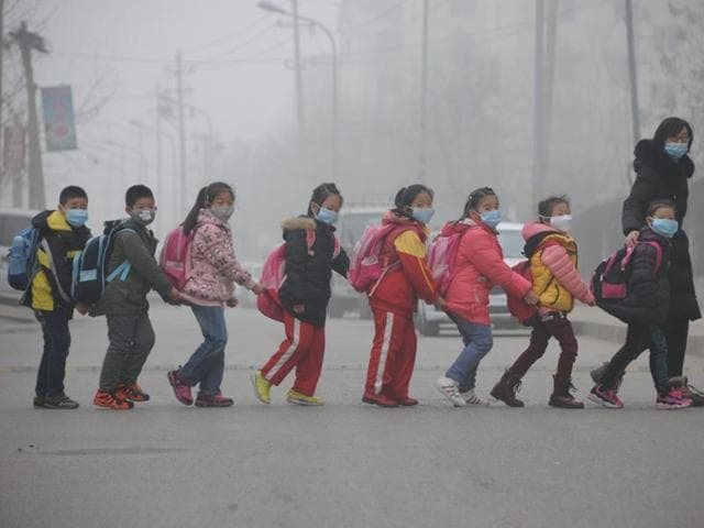 Students wearing face masks walk across the street in a line in Jinan, in east China's Shandong province amongst heavy air pollution.