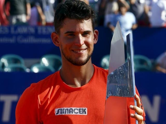 Austria's Dominic Thiem holds up the winner's trophy after defeating Spain's Nicolas Almagro (R) in the final of the Argentina Open in Buenos Aires on February 14, 2016.