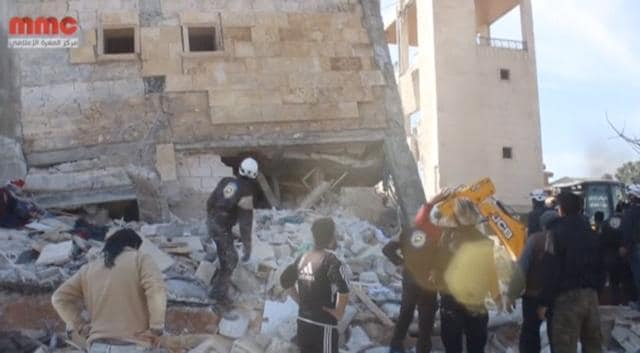 People gather near a destroyed building said to be a Medecins Sans Frontieres (MSF) supported hospital in Marat al Numan, Idlib.