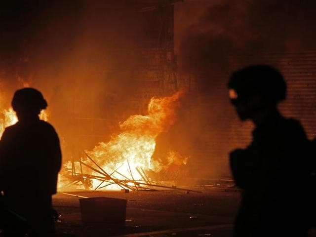 In this Tuesday, February 9, 2016 photo, police officers walk past a blazing fire set by protestors in Mong Kok district of Hong Kong.
