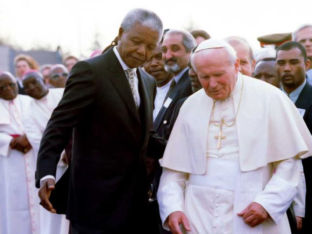 Former South African president Nelson Mandela guides late Pope John Paul II (R) after they met at Johannesburg International Airport September 16, 1994 during the pope's first official visit to the country.