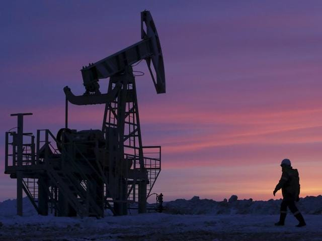 A worker walks past a pump jack on an oil field owned by Bashneft company near the village of Nikolo-Berezovka, northwest from Ufa, Bashkortostan in Russia