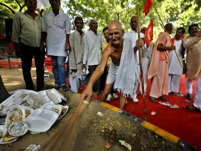 Dr Mahesh Chaturvedi, dressed like Mahatma Gandhi, sweeps a street in Jantar Mantar, New Delhi expressing his support for PM Modi's 'Swachh Bharat' campaign.